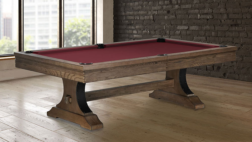 A wooden pool table with red felt set up in a large room.